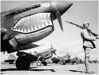 """Chinese soldier guarding US """"Flying Tiger"""" P-40 fighters during WWII"""
